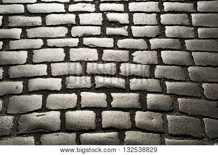 sunlight on cobblestone road. old stone texture