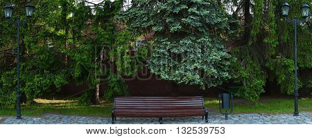 wooden bench in the spring park with two lampposts pines and red brick wall background. panorama
