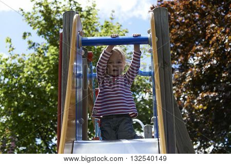 Happy two-year child girl on slide playground area