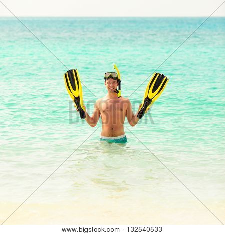Man, relaxing on the white sand beach in the clear sea water, lying on the water with yellow and black flippers fins and mask. After snorkeling Maldives beach Young