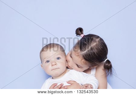 Little cute girl hugging little baby brother. Isolated over blue background