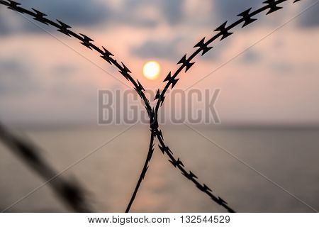 Barbed wire on sunset sky in the sea background