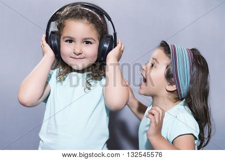 Smiling Girl Listening To Music In Headphones With Sister Screaming Nearby