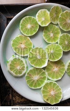 Slice of peeled green fresh lime on white plate. preparing for cooking in Thai style or to make fresh scent and be deodorizer for cozy Thai massage spa resort business. Thai culture style, flat lay and knolling concept.