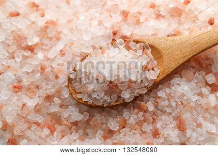 Pink Himalayan salt. Himalayan salt pile. Pink crystal salt  in wooden spoon. Close up Himalayan salt - pink and orange coarse crystals.