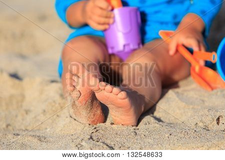little girl play with toys on beach, summer vacation