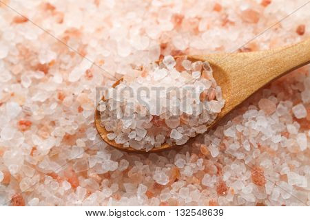 Pink Himalayan salt. Himalayan salt pile. Pink crystal salt  in wooden spoon. Close up Himalayan salt - pink and orange coarse crystals.