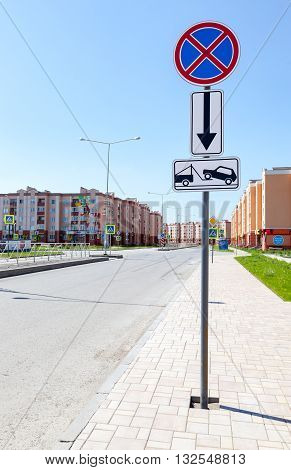 SAMARA RUSSIA - MAY 29 2016: Traffic sign prohibiting parking. Evacuation on tow truck with apartment buildings in background in summer day