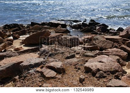 Rock seacoast with blue sea on background
