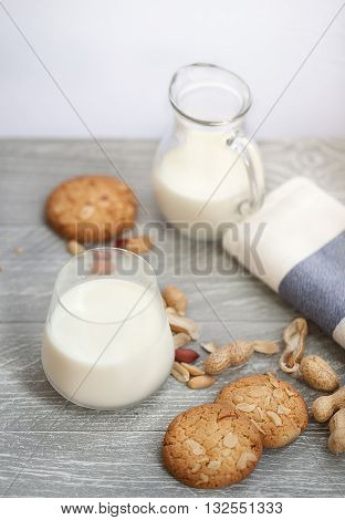 Milk with peanut biscuits on a wodden board
