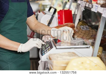 Salesman Weighting Cheese On Weight Scale
