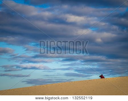 Unidentified lonely tourist walking among the stunning sand dunes in  the Natural Reserve of Dunes of Corralejo in Fuerteventura, Canary Islands, Spain