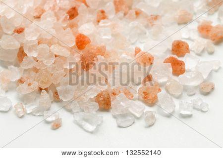 Pink Himalayan salt. Himalayan salt pile on white background. Pink crystal salt. Close up Himalayan salt - pink and orange coarse crystals.