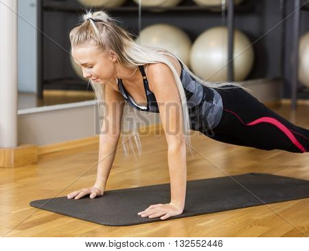 Active Woman Doing Pushups On Mat In Gym