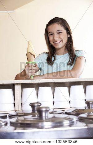 Smiling Girl Holding Vanilla Chocolate Ice Cream Cone At Counter