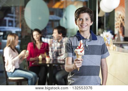 Smiling Boy Holding Vanilla Ice Cream Cone In Parlor