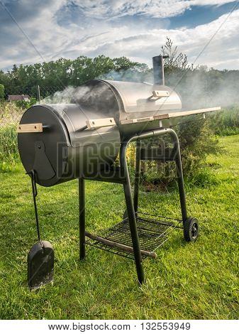Barbeque meal being prepared using black grill with chimney in the backyard