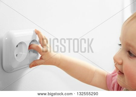 Little child's hand playing with power socket, closeup