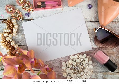 Ladies background - shoes, lipstick, nail polish, earrings and white wooden background. Top view