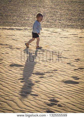 Little boy walking up the sand on the sand dunes in  the Corralejo Dunes National Park, Fuerteventura, Canary Islands, Spain
