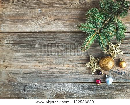 Christmas or New Year rustic wooden background with toy decorations and fur tree branch, top view, copy space