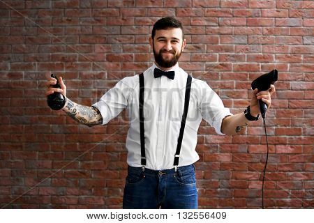 Professional hairdresser with hairdryer and spray on brick wall background