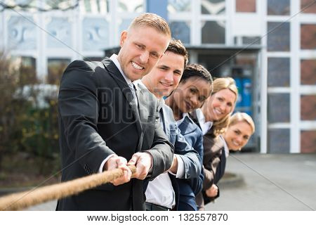 Group Of Happy Multiethnic People Playing Tug Of War
