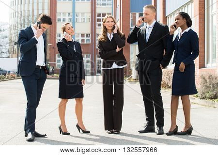 Group Of Professional Businesspeople Talking On Mobile Phones;Outdoor