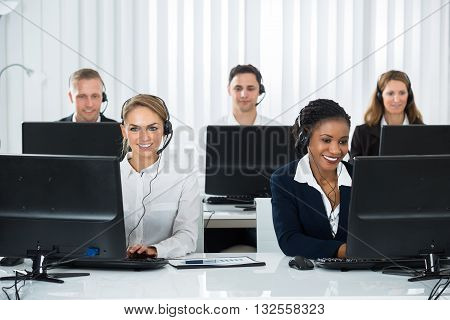 Team Of Call Center Operators Working On Computers At Workplace