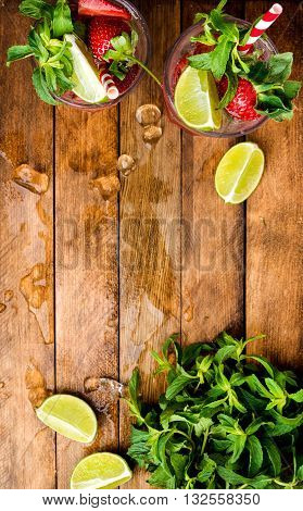 Strawberry mojito summer cocktails with mint and lime in glasses. Wooden background, top view, copy space