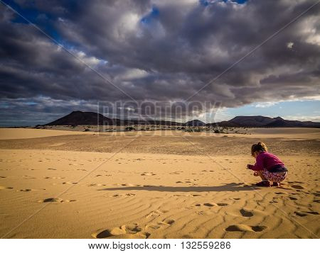 Little girl picking up small stones from the sand on the sand dunes in  the Natural Reserve of Dunes in Corralejo, fuerteventura, Canary Islands, Spain