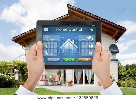 Close-up Of A Hand Holding Digital Tablet With Home Control System In Front Of House