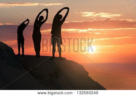 Silhouette Of A Family Stretching On A Hill Against Climatic Sky