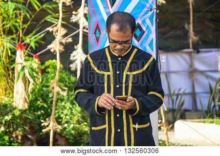 Penampang,Sabah-May 31,2016:A Kadazandusun man ethnic playing with handphone duringHarvest Festival celebration May 31,2016 in Kota Kinabalu, Sabah Borneo, Malaysia.