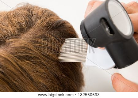 Close-up Of Doctor Hand With Comb And Dermatoscope Doing Treatment Of Patient's Hair