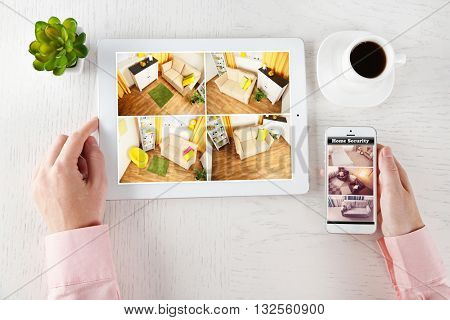 Male hands with tablet and phone on white table. Home security system concept