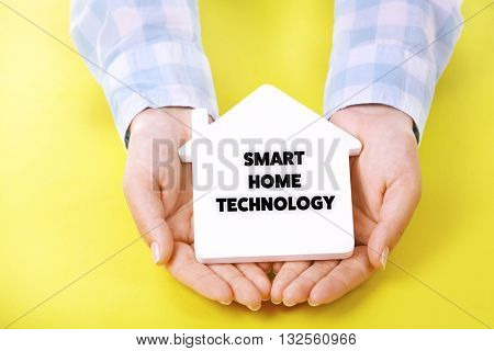 Smart home technology concept. Female hands holding house on yellow background