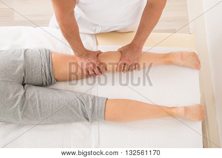 High Angle View Of Therapist Giving Leg Massage In Spa