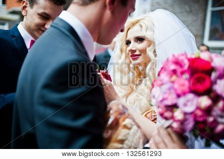Bride has boutonniere for groom at outdoors