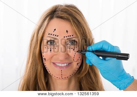 Close-up Of Happy Mature Woman With Perforation Lines Marked On Face