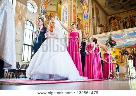 Stylish groomsmen and bridesmaids with wedding couple at the church