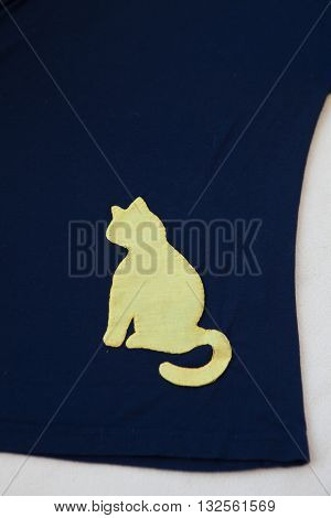 Navy blue tshirt with yellow cat sawed on white background