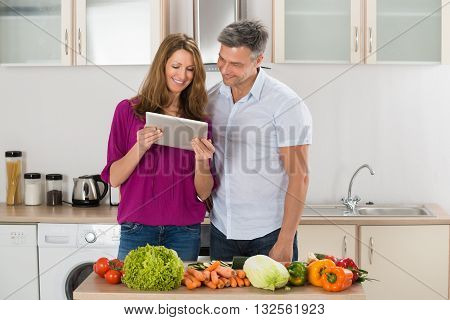 Happy Couple Looking At Digital Tablet With Vegetables On Countertop In Kitchen