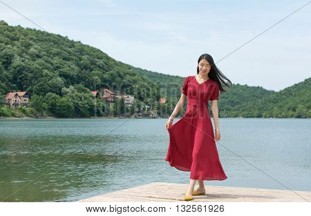Fashionable Woman Standing In Front Of A Lake
