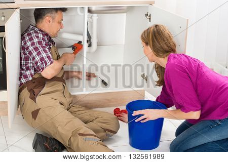 Male Plumber Repairing Pipe Under Sink While Woman Standing In Kitchen