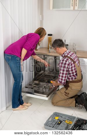 Woman Looking At Male Repairman Checking Dishwasher With Digital Multimeter