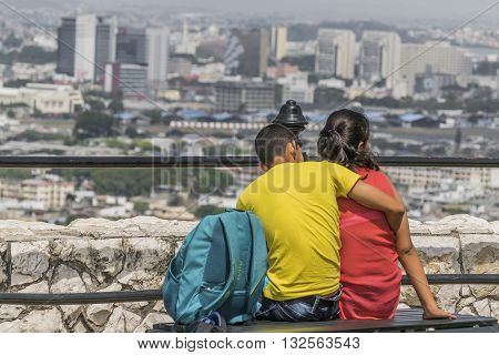 GUAYAQUIL, ECUADOR, CIRCA OCTOBER -2015 - Back view of teen couple hugginG at with at the top of a hill at Cerro Santa Ana in Guayaquil Ecuador.