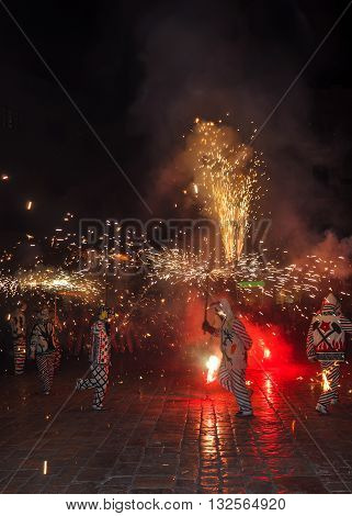 Traditional catalan spectacle called Correfocs (fire runs) or Ball de Diables (Devils' Dance). Group of individuals dressed as devils and dancing with lighting fireworks fixed on devil's pitchforks. Reus Spain. Vertical.