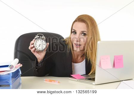 worried attractive blond businesswoman holding alarm clock sitting at office desk working with computer laptop in long hours of work and business stress concept isolated on white background