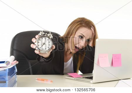 worried attractive blond businesswoman holding alarm clock overwhelmed in stress working with computer laptop in deadline project and business stress concept isolated on white background